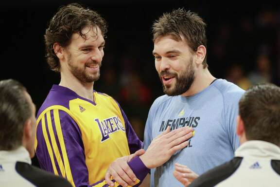 FILE - In this Nov. 15, 2013, file photo, Los Angeles Lakers' Pau Gasol, left, of Spain, and his brother, Memphis Grizzlies' Marc Gasol talk to referees before an NBA basketball game in Los Angeles. The NBA announces, Thursday, Jan. 22, 2015,  the 10 players voted by fans to start in next month's All-Star game in New York, with brothers Pau and Marc Gasol in position to face each other after the last update. (AP Photo/Jae C. Hong, File)