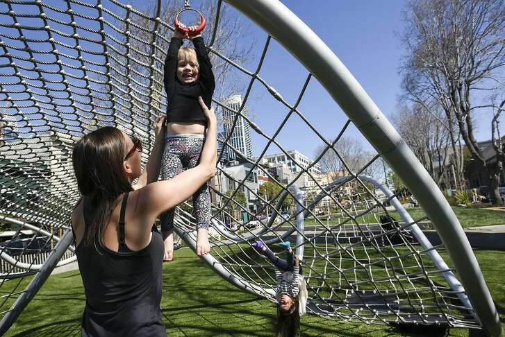 Caroline Dunivant lifts up her daughter Lula Dunivant, 2 1/2, onto the children's playground structure as they visit the newly designed and renovated South Park in San Francisco, CA, on Friday March 17, 2017.