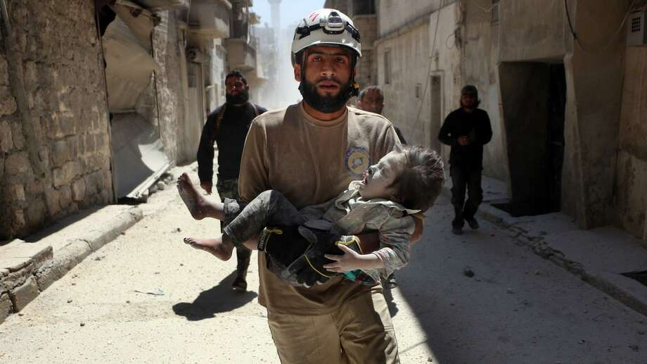 "A volunteer in Aleppo, Syria, carries an injured child after an air strike in the Oscar-winning documentary short, ""The White Helmets,"" streaming on Netflix. Photo: Beha El Halebi / Contributed Photo / Connecticut Post Contributed"