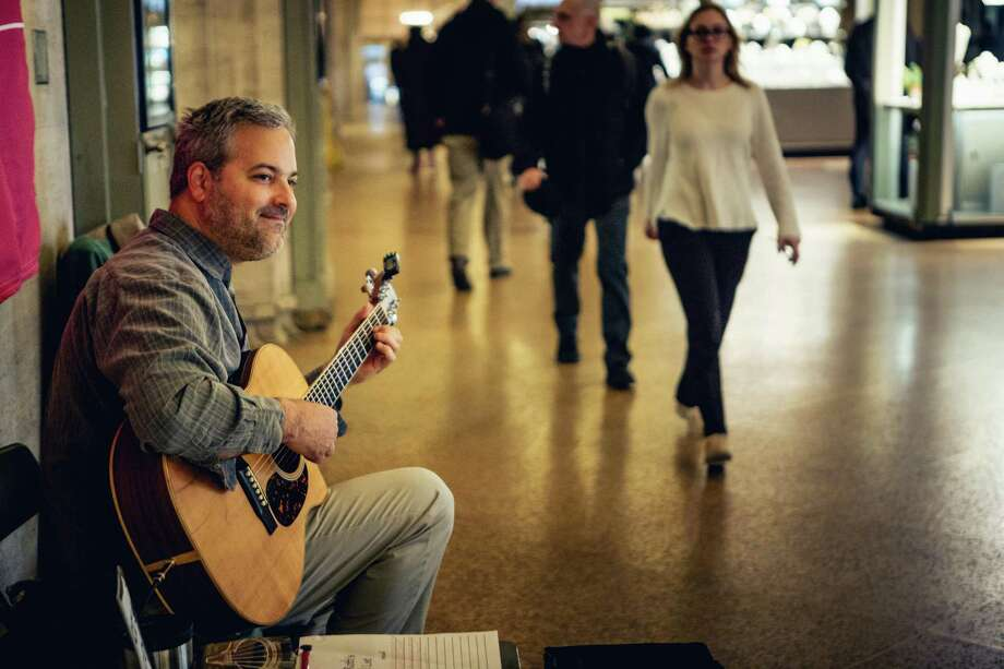 Glenn Roth plays his guitar at his weekly New York City gig inside Grand Central. Photo: Christopher Setter / For Hearst Connecticut Media / Christopher Setter/For Hearst Connecticut Media