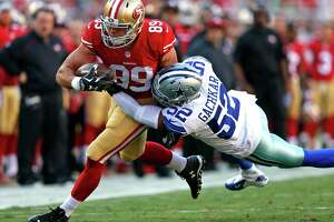 San Francisco 49ers' Vance McDonald is brought down by Dallas Cowboys' Andrew Gachkar in 1st quarter during NFL preseason game at Levi's Stadium in Santa Clara, Calif., on Sunday, Aug. 23, 2015.