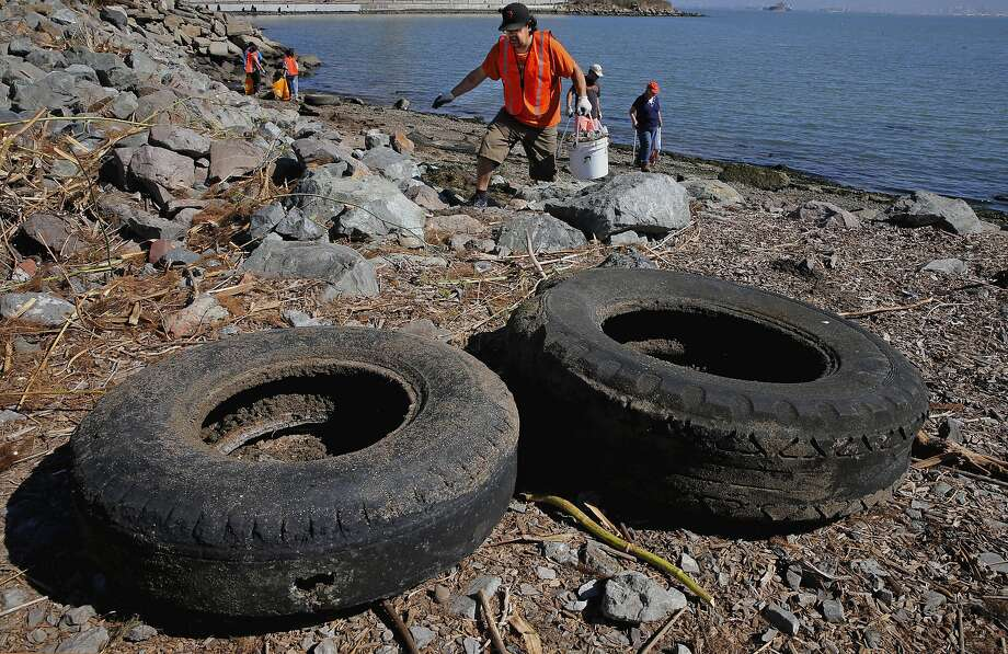 Jorge Gonzalez, searches for debris near collected old tires at Warm Water Cove, in San Francisco, Calif., as he joins hundreds of volunteers participating in the Community Team's Coastal Cleanup Day, at different locations along the San Francisco Bay shoreline, on Sat. September 19, 2015. Photo: Michael Macor, The Chronicle