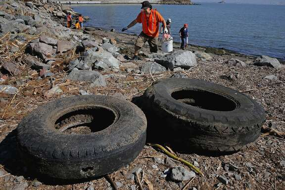 Jorge Gonzalez, searches for debris near collected old tires at Warm Water Cove, in San Francisco, Calif., as he joins hundreds of volunteers participating in the Community Team's Coastal Cleanup Day, at different locations along the San Francisco Bay shoreline, on Sat. September 19, 2015.