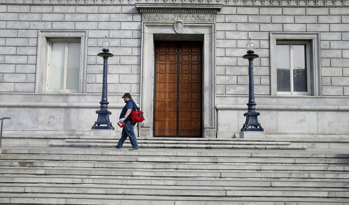 Jose Luis Guzman, from the Department of Public Health, looks for discarded hypodermic needles on the steps of the Asian Art Museum in San Francisco, Calif. on Thursday, March 16, 2017.