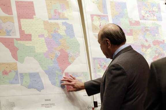 """A federal court in San Antonio has said three congressional districts in Texas were gerrymandering to negatively affect Latinos. State Sen. Juan """"Chuy"""" Hinojosa looks at maps on display prior to a Senate Redistricting committee hearing in 2013, in Austin, Texas."""