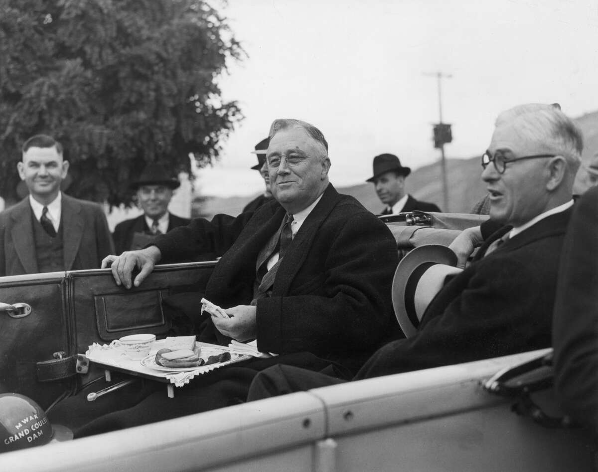 Oct. 2, 1937: President Franklin D. Roosevelt smiles as he eats a sandwich from a tray in the back of a car, on a visit to the Grand Coulee Dam. The Woods family, owners of the Wenatchee World for 111 years, were generally Republicans, but found a champion of their dam in this Democratic president.