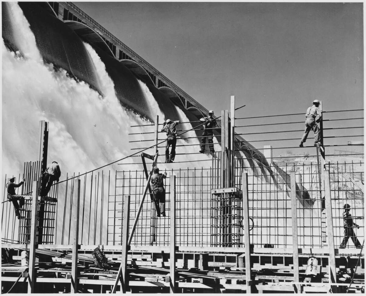Workers construct a rebar structure as the Columbia River cascades over an enormous spillway at the Grand Coulee Dam. Washington, USA, 1936-1946.   Location: Washington, USA. (Photo by Library of Congress/Corbis/VCG via Getty Images)