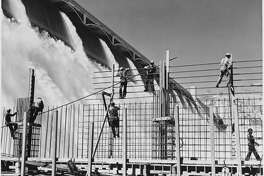 Workers construct a rebar structure as the Columbia River cascades over an enormous spillway at the Grand Coulee Dam. Washington, USA, 1936-1946. | Location: Washington, USA.    (Photo by Library of Congress/Corbis/VCG via Getty Images)