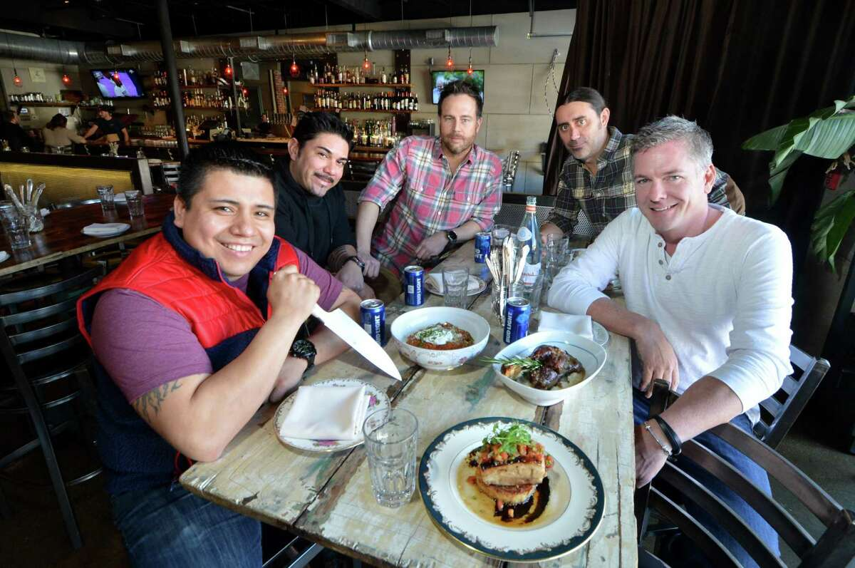 Gathered around a vintage barn door that serves as a dining table, the community minded owners of The Spread in SoNo, Chef Owner Carlos Baez, Owners Andrey Cortes, Chris Rasile, Shawn Longyear and Chris Hickey, on Thursday March 16, 2017 in Norwalk Conn.