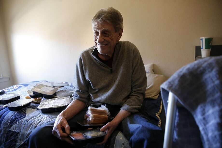 Tenderloin resident David Drees, 70, sorts through his items after delivery of his weekend Meals on Wheels. Photo: Michael Macor, The Chronicle