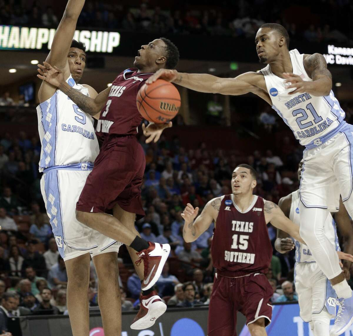 North Carolina's Seventh Woods (21) blocks a shot by Texas Southern's Demontrae Jefferson (3) as Tony Bradley (5) defends during the first half in a first-round game of the NCAA men's college basketball tournament in Greenville, S.C., Friday, March 17, 2017. (AP Photo/Chuck Burton)