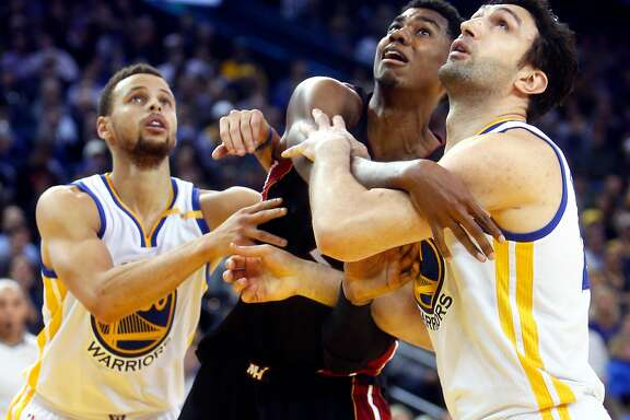 Golden State Warriors' Zaza Pachulia and Stephen Curry battle Miami Heat's Hassan Whiteside for position in 4th quarter of Warriors' 107-95 win in NBA game at Oracle Arena in Oakland, Calif., on Tuesday, January 10, 2017.