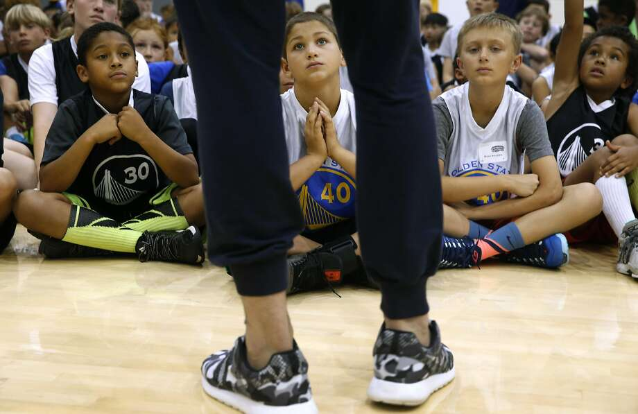 Kids attending a youth basketball camp look up to 6-foot-11-inch Zaza Pachulia at the Warriors practice facility in Oakland. Photo: Paul Chinn, The Chronicle