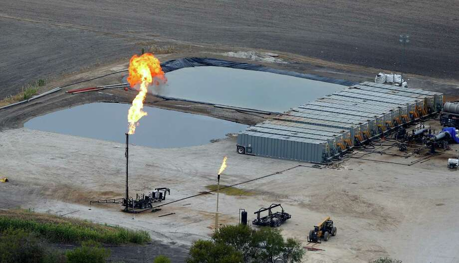 Water retention ponds are seen behind a gas flare, also known as a flare stack, in a Dec. 13, 2013, aerial picture taken in the Eagle Ford Shale region near Karnes City. Photo: William Luther /San Antonio Express-News / © 2013 San Antonio Express-News