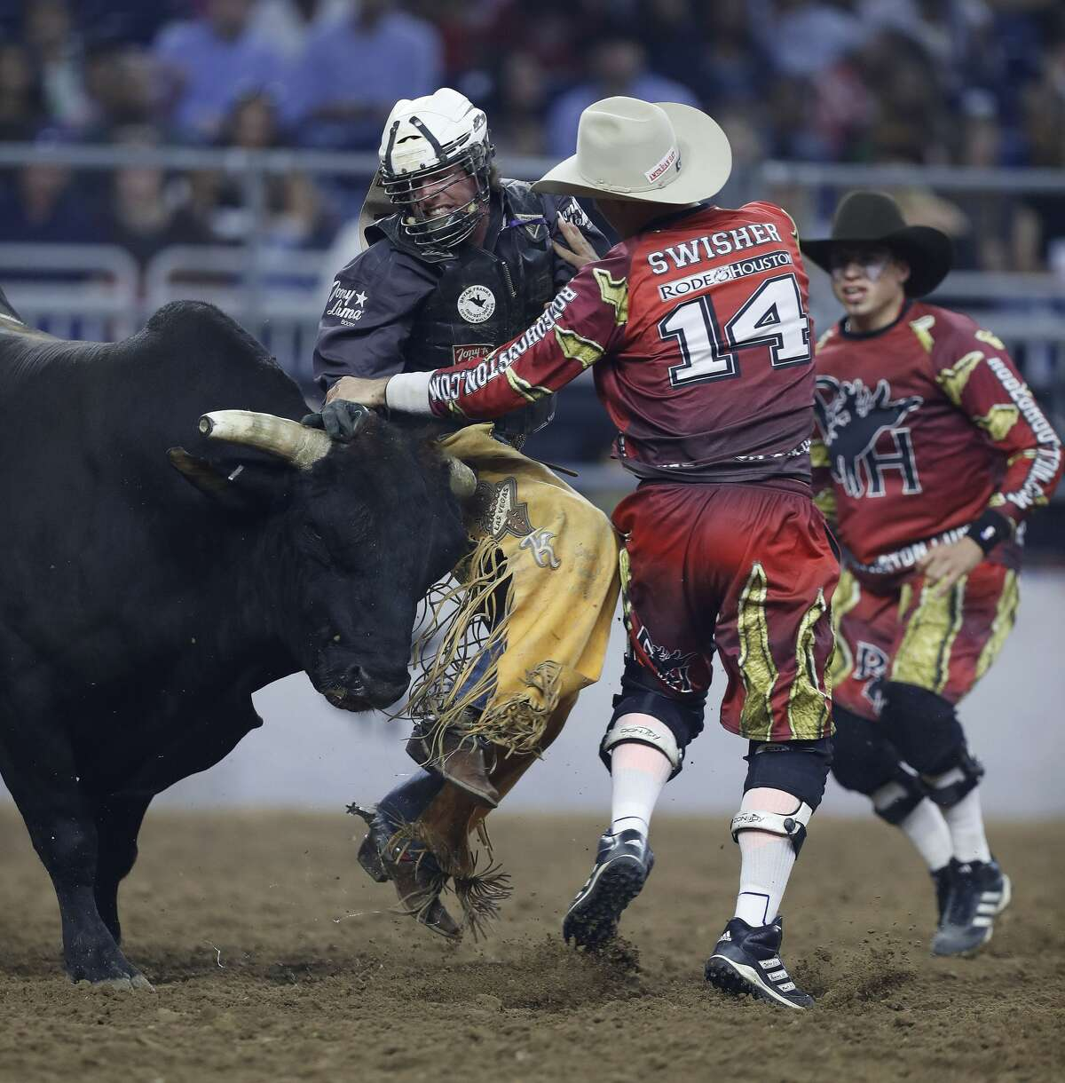 Trevor Kastner gets horned by Bucket Head the bull as bullfighter Chuck Swisher comes in to help him in the bull riding competition during the Super Series IV, round 2, at NRG Stadium, Friday, March 17, 2017, at the Houston Livestock Show and Rodeo, in Houston. ( Karen Warren / Houston Chronicle )