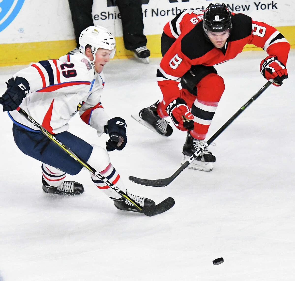 Springfield Thunderbirds' #29 Dryden Hunt, left, and Albany Devils #8 Josh Jacobs race for the puck during Friday's game at the Times Union Center March 17, 2017 in Albany, NY. (John Carl D'Annibale / Times Union)