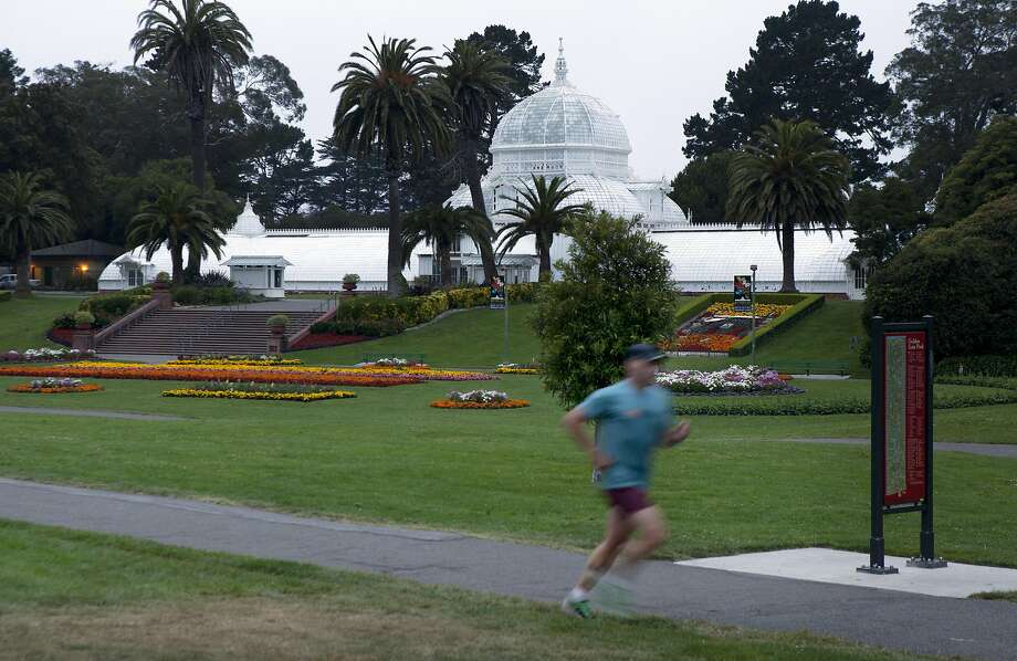 A jogger runs in front of the Conservatory of Flowers on  John F. Kennedy in Golden Gate Park after the sun went down in San Francisco, Calif., on Sunday, July 21, 2013. Supervisor Scott Wiener will introduce legislation Tuesday setting uniform hours of 5 a.m. to midnight for all San Francisco parks, most of which are never closed. The idea is that it will make it easier for police and park patrol units to keep people out of the parks late at night when vandalism and metal theft occurs. Photo: Carlos Avila Gonzalez, The Chronicle