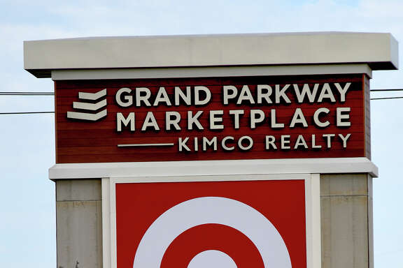 Workers put the finishing touches on a sign at Grand Parkway Marketplace I.