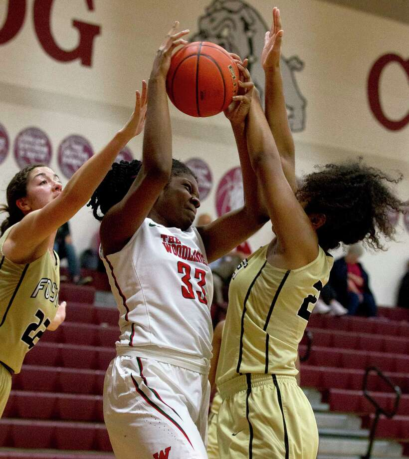 The Woodlands center Whitney Ozoani  (33) fights for position as she is double teamed by Foster forwards Miranda Stephens (22) and Summer Kimble (23) during the second quarter of a high school girls basketball game at the Magnolia Holiday Hoop Fest Thursday, Dec. 29, 2016, in Magnolia. The Woodlands defeated Foster 60-37 in the semifinals of the golf bracket to advance to Friday's final at noon. Photo: Jason Fochtman, Staff Photographer / Houston Chronicle
