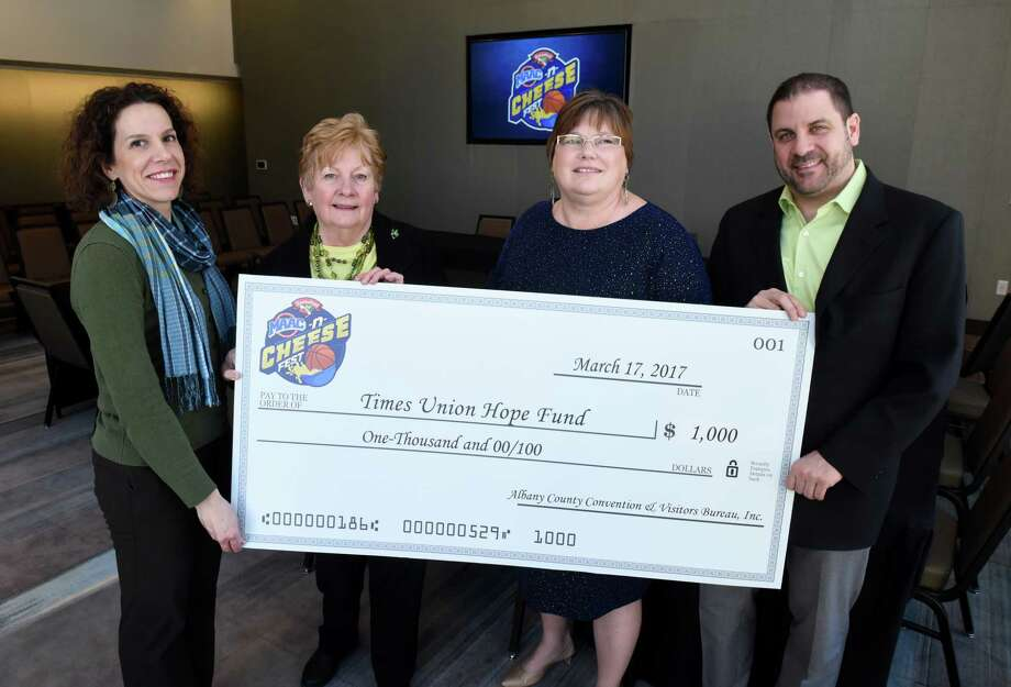 Francesca Mancino of Hannaford Supermarkets, left, Michele Vennard, president of the Albany County Conventions and Visitors Bureau, second from left, and Doug McClaine, general manager of the Capital Center and Times Union Center, right, present a $1,000 check to the Times Union Hope Fund, which was accepted by Ruth Fantasia, human resources director for the Times Union, second from right, on Friday, March 17, 2017, at the Capital Center in Albany, N.Y. The money was donated from part of proceeds collected from the Hannaford MAAC-n-Cheese Fest which was held at the Capital Center two weeks ago. It was the first event to be held at the Capital Center on Eagle St. (Will Waldron/Times Union) Photo: Will Waldron / 20040001A