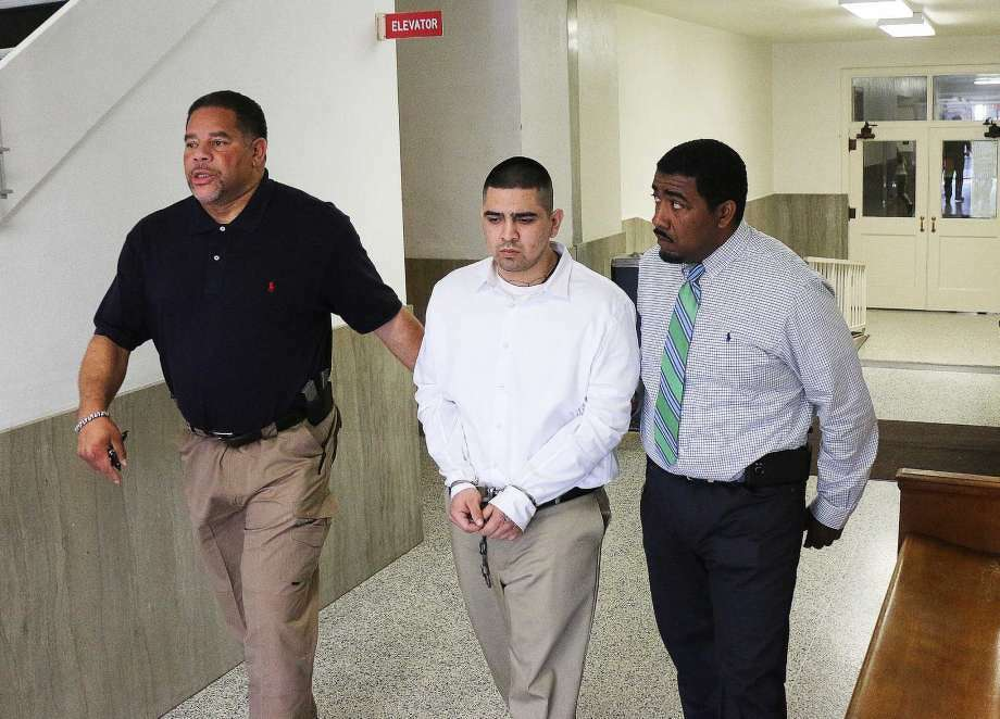 Roberto Ismael Alvarado Jr. is led away from the Liberty County Courthouse by Robert Harper and Chadwick Elmore, bailiffs for the 253rd State District Court. Alvarado was sentenced to 65 years in prison Wednesday for his part in the Dec. 16, 2015 murder of a convenience store clerk in Cleveland. Three other young men accused of participating in the crime have accepted plea agreements and are awaiting sentencing.