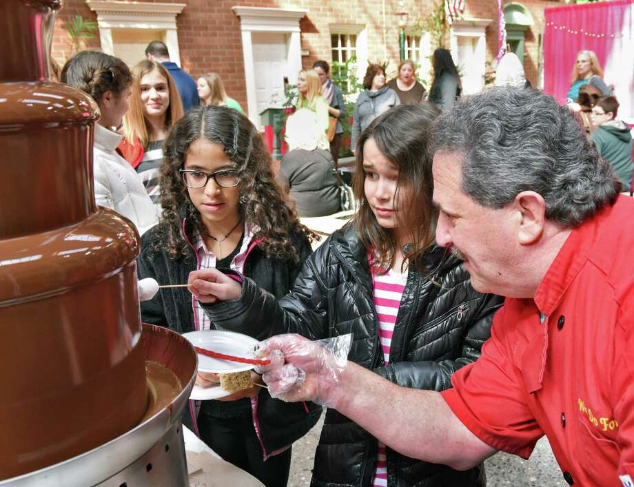 Ten-year-olds Hanna Gialil, left, and Coco Offord, both of Greenfield, are introduced to the chocolate fountain by Craig Wander of We Do Fondue of Albany during the Albany Wine & Chocolate Festival Saturday March 18, 2017 in Colonie, NY.  (John Carl D'Annibale / Times Union) Photo: John Carl D'Annibale / 20039992A