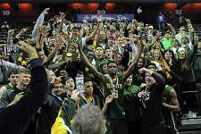 Trinity Catholic Dimitry Moise, center, celebrates with fans following the Crusaders 61-52 win over Westbrook in the CIAC Class S boys basketballl final at The Mohegan Sun Arena in Uncasville, Conn. on March 18, 2017.
