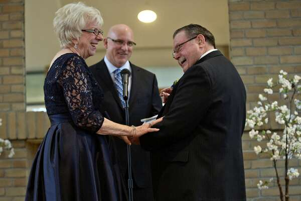 Bride Nancy Swift, left, and her groom Keith Bauerle, right, share a laugh as Keith prepares to place a ring on Nancy's finger during their wedding ceremony on Saturday at Riverside Place Senior Living Community in downtown Midland. Midland Nazarene lead pastor Dave Anderson, center, looks on. The two were married more than a year after meeting as residents at Riverside.