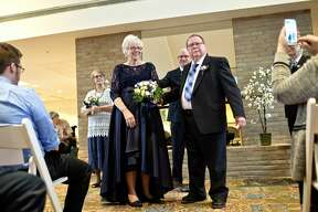 Nancy Swift, left, and Keith Bauerle face the crowd after officially being married on Saturday at Riverside Place Senior Living Community in downtown Midland. The two were married more than a year after meeting as residents at Riverside.