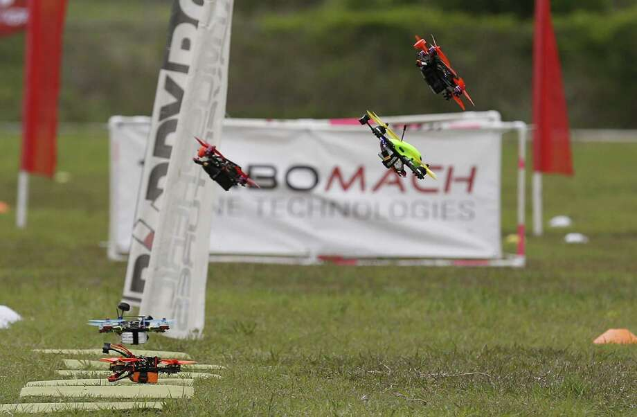 Drones are launched from the starting line during a practice session as drone racers from the area gather at Solms Park in New Braunfels, Texas for a competition qualifier on Saturday, Mar. 18, 2017. With their toolboxes, extra batteries and a cornucopia of drone parts, competitors practiced their best routes around a course of dips, dives and challenging obstacles before starting the qualifying rounds. With speeds reaching 70-80 miles per hour, racers rely on a good signal through their video FPV (first person view) googles and their cat-like reflexes to remotely fly the drones along the course. (Kin Man Hui/San Antonio Express-News) Photo: Kin Man Hui, Staff / San Antonio Express-News / ©2017 San Antonio Express-News
