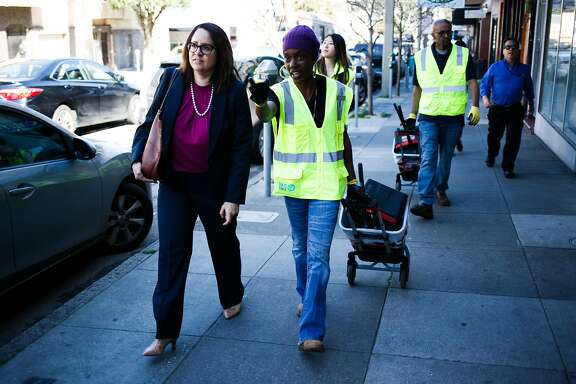 Safonya Crawford, center, shows Fix-It Director, Sandra Zuniga, left, areas of issues on 9th Avenue in San Francisco, Calif. Friday, March 17, 2017.