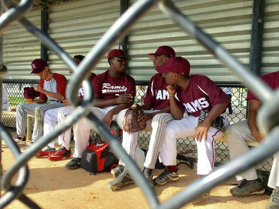 Ernest Nixon, center left, engages in some dugout chatter with his baseball teammates for Palm Beach Lakes Community High School, whose median household income is less than $33,000. Photo credit: Hunter Atkins