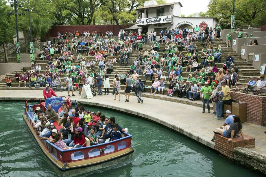 A river boat passes by as people listen to Ledbetters during the 2017 Harp & Shamrock Society of Texas St. Patrick's Day festivities in San Antonio, Texas on March 18, 2017. Ray Whitehouse / for the San Antonio Express-News Photo: Ray Whitehouse, Photographer / For The San Antonio Express-News