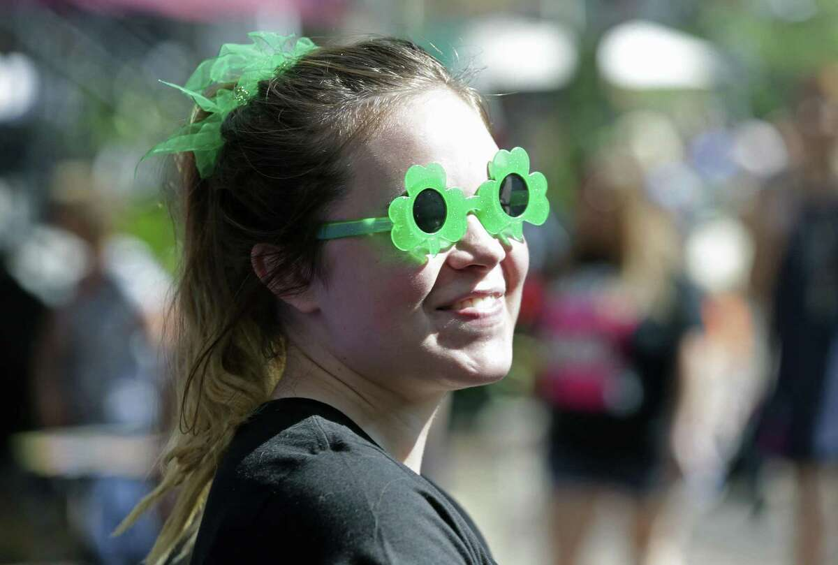 Brianna Peterson glances around from behind special festive sunglasses as St. Patrick's Day is celebrated on the Riverwalk with both the river and the beer dyed green for the occasion on March 18, 2017.