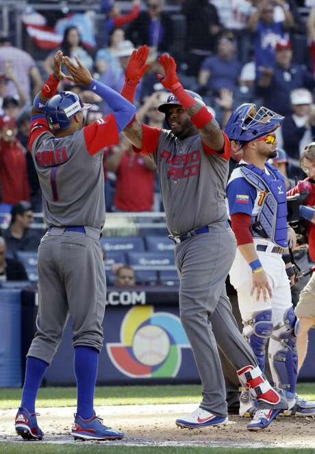 Puerto Rico's Kennys Vargas, center right, is greeted by teammate Carlos Correa (1) after hitting a two-run home run against Venezuela during the ninth inning of a second-round World Baseball Classic baseball game Saturday, March 18, 2017, in San Diego. (AP Photo/Gregory Bull) Photo: Gregory Bull/Associated Press