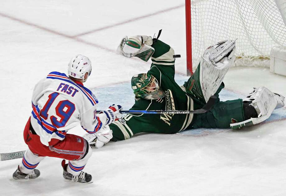 A falling Minnesota Wild goalie Devan Dubnyk, right, blocks a shot by New York Rangers' Jesper Fast during the first period of an NHL hockey game Saturday, March 18, 2017, in St. Paul, Minn. (AP Photo/Jim Mone) ORG XMIT: MNJM103 Photo: Jim Mone / Copyright 2017 The Associated Press. All rights reserved.