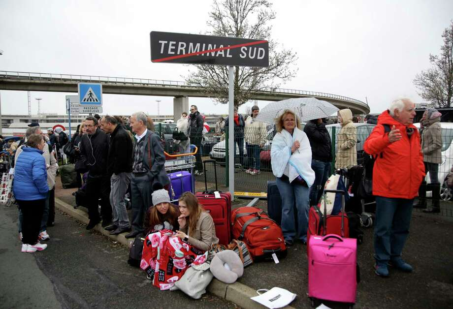 Travelers wait outside the Orly airport , south of Paris, Saturday, March, 18, 2017. A man was shot dead after wrestling a soldier to the ground at Paris' Orly Airport and trying to take her rifle, officials said. No one else in the busy terminal was hurt, but thousands of travelers were evacuated and flights were diverted to the city's other airport. (AP Photo/Thibault Camus) ORG XMIT: PAR127 Photo: Thibault Camus / Copyright 2017 The Associated Press. All rights reserved.