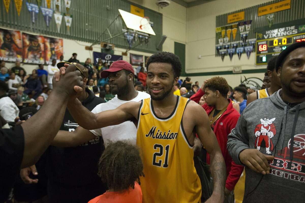 Mission�s Niamey Harris (21) basks in the congratulatory hugs after his team defeated Vanden in a boys' high school basketball game on Saturday, March 18, 2017 in Fairfield, Calif. Mission won 72-68.