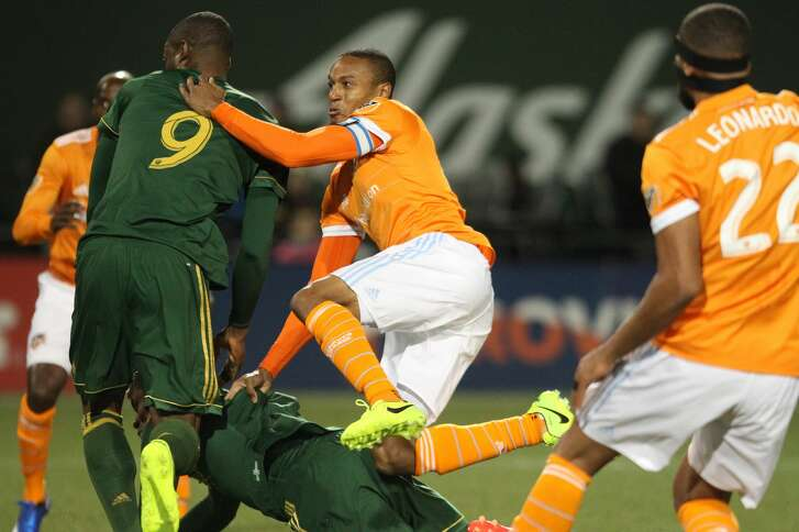 Houston Dynamo midfielder Ricardo Clark crashes through several Portland Timbers during the first half of an MLS soccer match Saturday, March 18, 2017, in Portland, Ore. (Pete Christopher/The Oregonian via AP)/The Oregonian via AP)