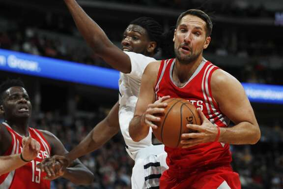Houston Rockets forward Ryan Anderson, front, pulls in a rebound in front of Denver Nuggets forward Kenneth Faried (35) and Rockets center Clint Capela, of Switzerland, during the second half of an NBA basketball game Saturday, March 18, 2017, in Denver. The Rockets won 109-105. (AP Photo/David Zalubowski)
