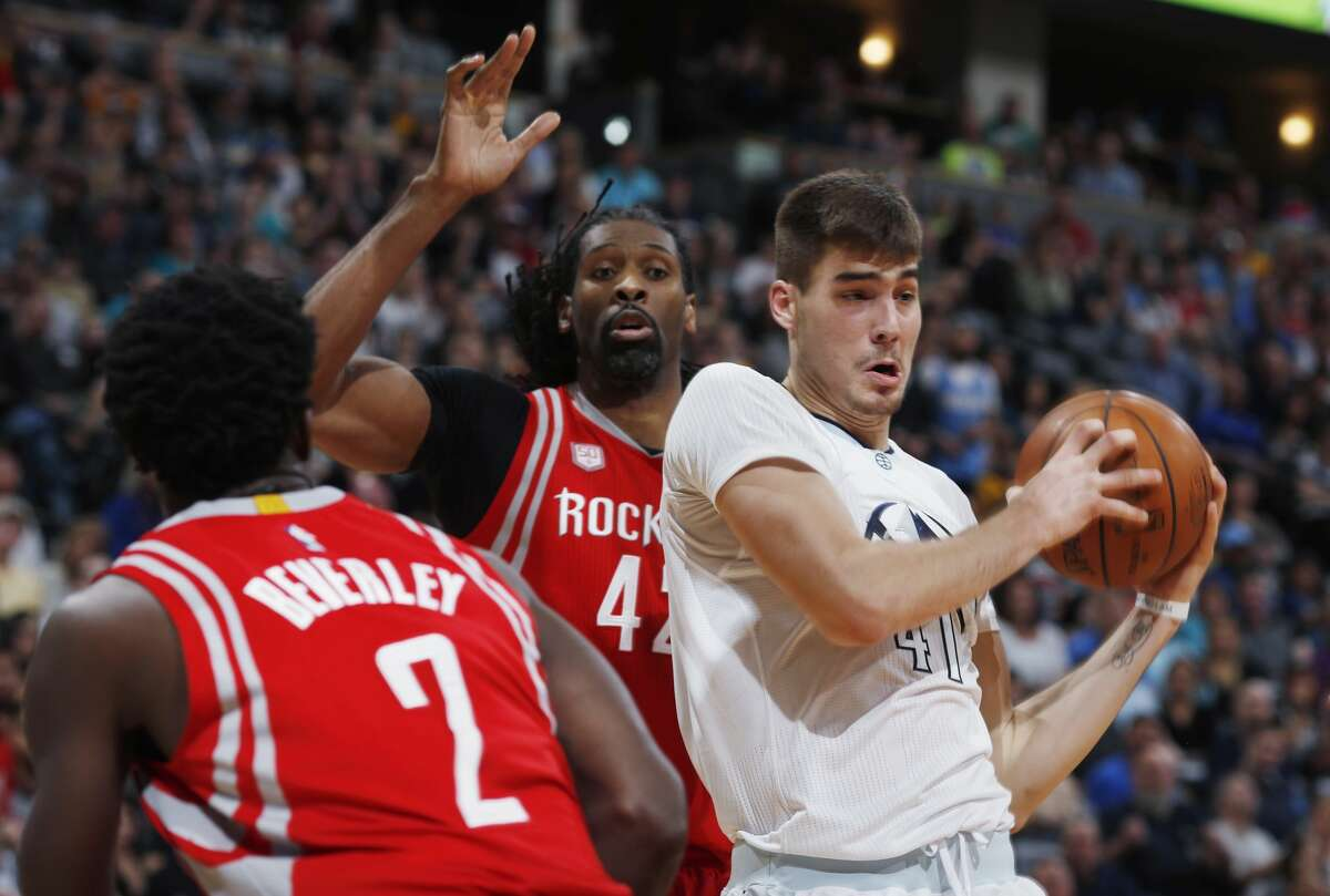 Denver Nuggets forward Juancho Hernangomez, right, of Spain, pulls in a rebound as Houston Rockets guard Patrick Beverley, left, and center Nene Hilario, of Brazil, defend during the second half of an NBA basketball game Saturday, March 18, 2017, in Denver. The Rockets won 109-105. (AP Photo/David Zalubowski)