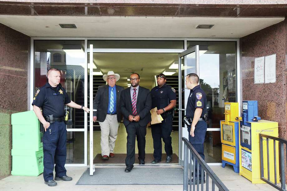 David Earl Mitchell walks out of the doors of the Liberty County Courthouse on Thursday afternoon in handcuffs, headed to county jail temporarily before being transferred to a location in the Texas prison system. Liberty County Sheriff's Corporal Paul Young (left) and Sgt. Tim Niemeyer hold the door for Mitchell, Capt. Don Neyland (with hat) and Deputy Josh Leal. Photo: David Taylor