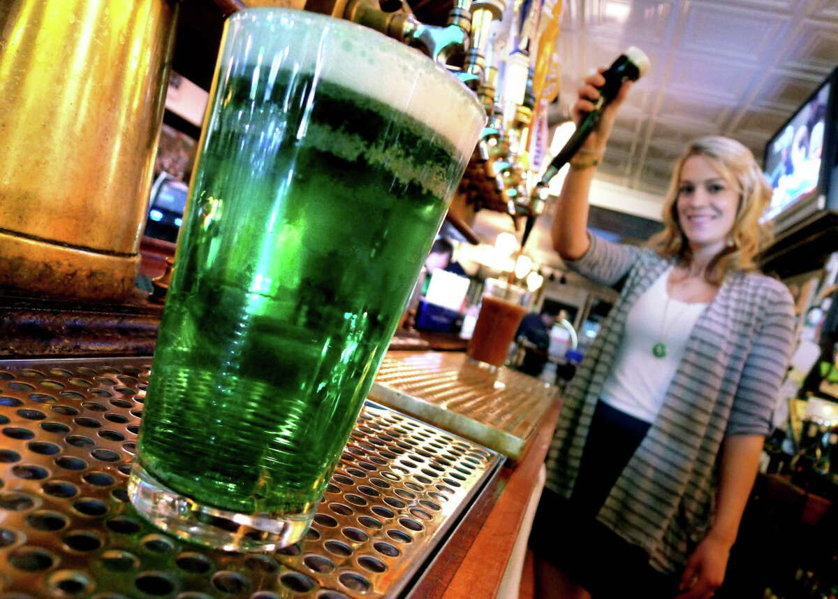 McGeary's bartender Lauren Bryant pours a pint of Guinness after pouring a pint of green beer at the downtown Albany establishment Wednesday March 16,2011.( Michael P. Farrell/Times Union )