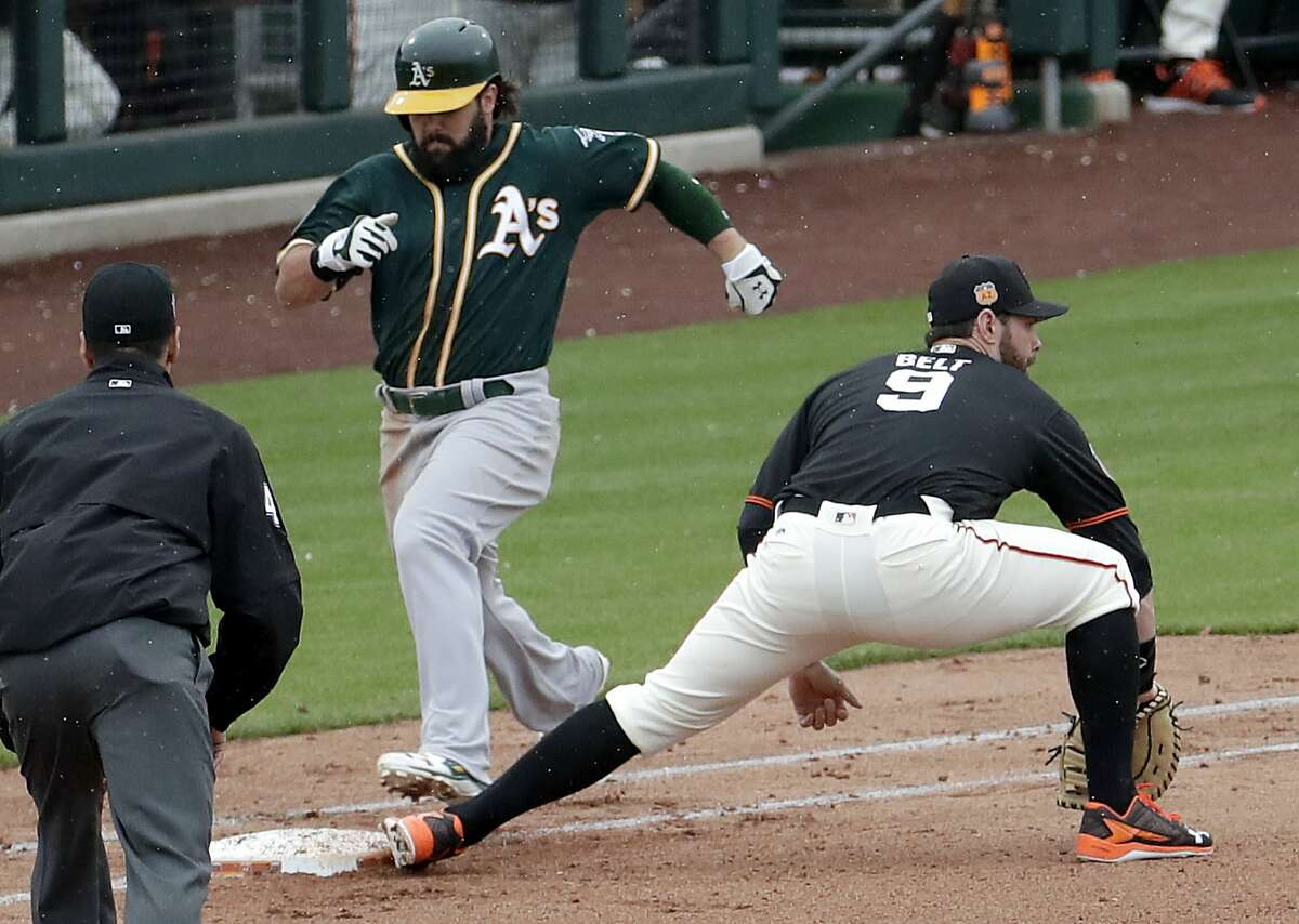 Oakland Athletics' Jaff Decker beats out the throw for a base hit as San Francisco Giants first baseman Brandon Belt (9) makes the catch during the third inning of a spring training baseball game, Monday, Feb. 27, 2017, in Scottsdale, Ariz. (AP Photo/Matt York)