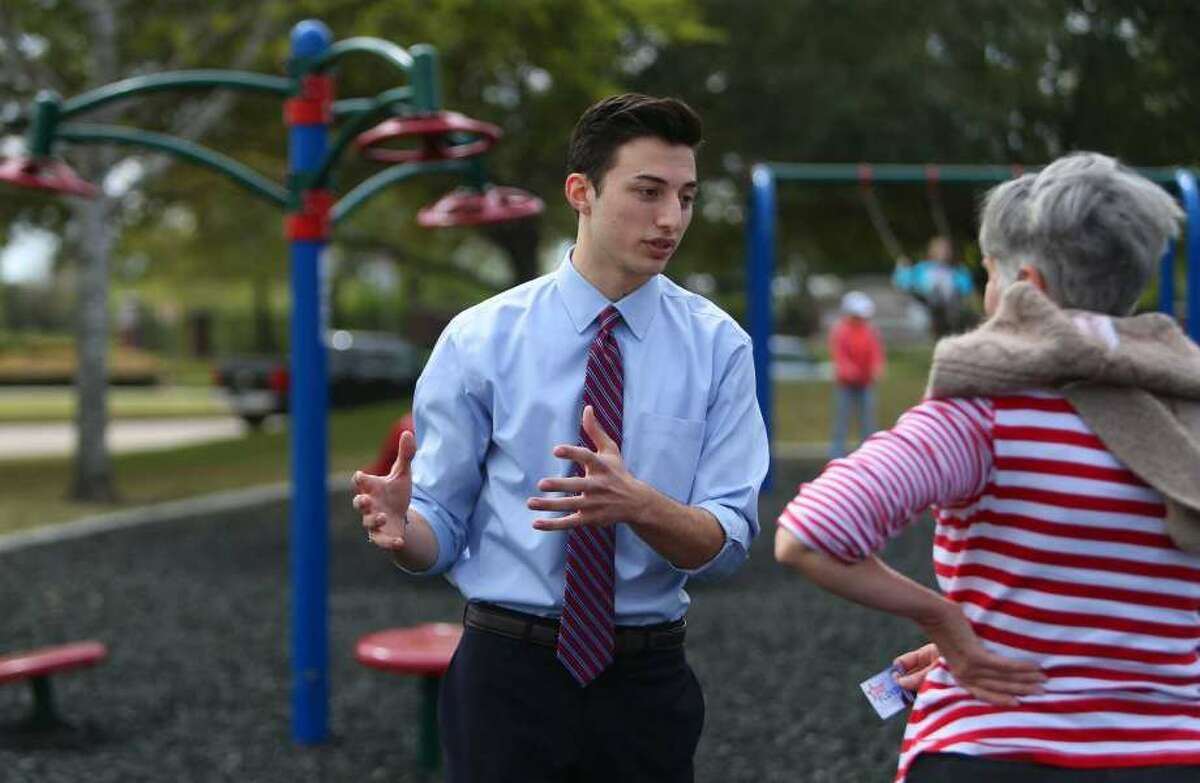 Mike Floyd, an 18-year-old senior at Dawson High School, speaks to a potential voter about his run for the Pearland Independent School District's Board of Trustees, Wednesday, March 15, 2017, at Silverlake Park.