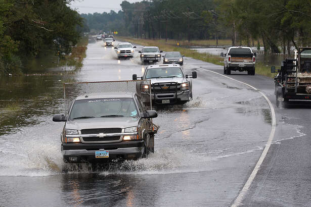 Traffic shifts lanes around a curve to avoid flood waters on Highway 326 near Sour Lake Monday morning. Hardin County received five inches of rain over the weekend prompting several campuses to cancel school on Monday. Photo taken Monday, November 02, 2015 Guiseppe Barranco/The Enterprise