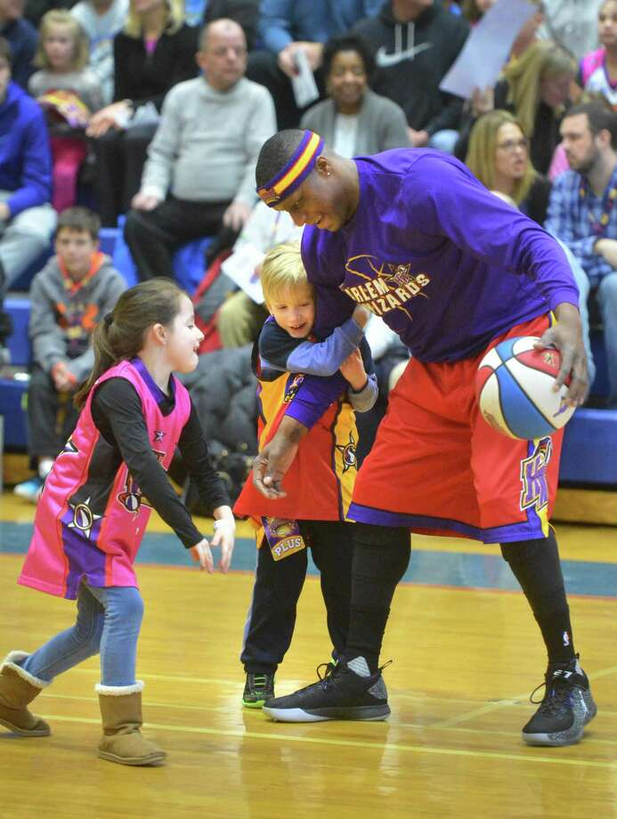 "Harlem Wizards Leon ""Space Jam"" Sewwll is double-teamed by a determined Braydon Charlip holding onto his arm and Bella Calese who is hoping to get the ball away from him. Kids played with team members during a meet greet and play session at the Fox Run Elementary School fundraiser featuring the Harlem Wizards vs The Foxy Trotters, comprised of school staff and city officials at Brien McMahon High School gym on Sunday March 19, 2017 in Norwalk. Photo: Alex Von Kleydorff / Hearst Connecticut Media / Norwalk Hour"