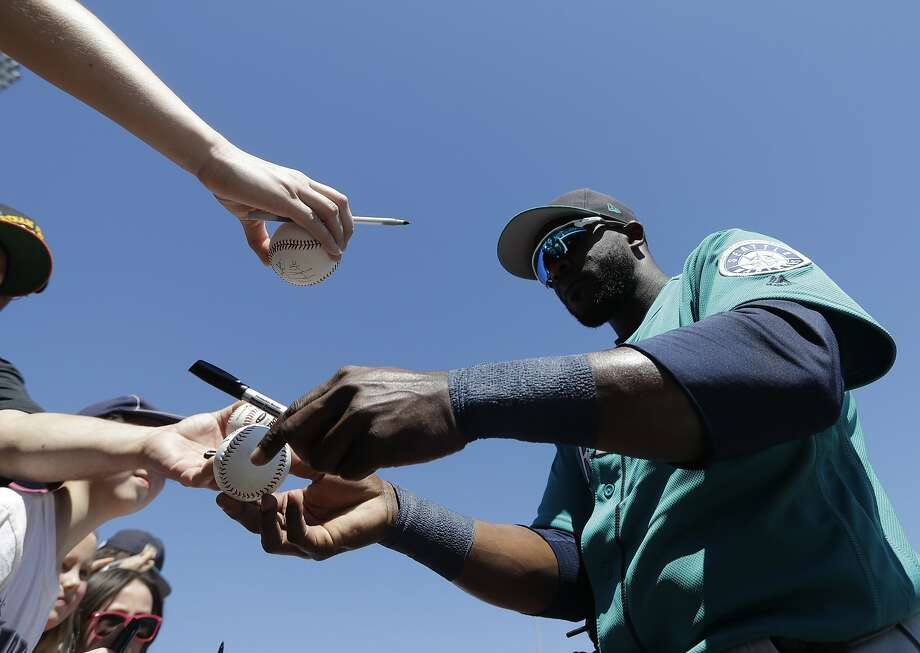 On a hot sunny day with clear blue skies in Surprise, Ariz., Seattle Mariners' Guillermo Heredia oufielder signs autographs for fans. Photo: Darron Cummings, Associated Press
