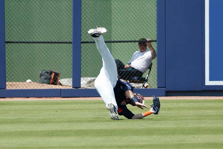 Astros left fielder Josh Reddick takes a rough-and-tumble approach to snagging a ball off the bat of the Yankees' Greg Bird in the fifth inning