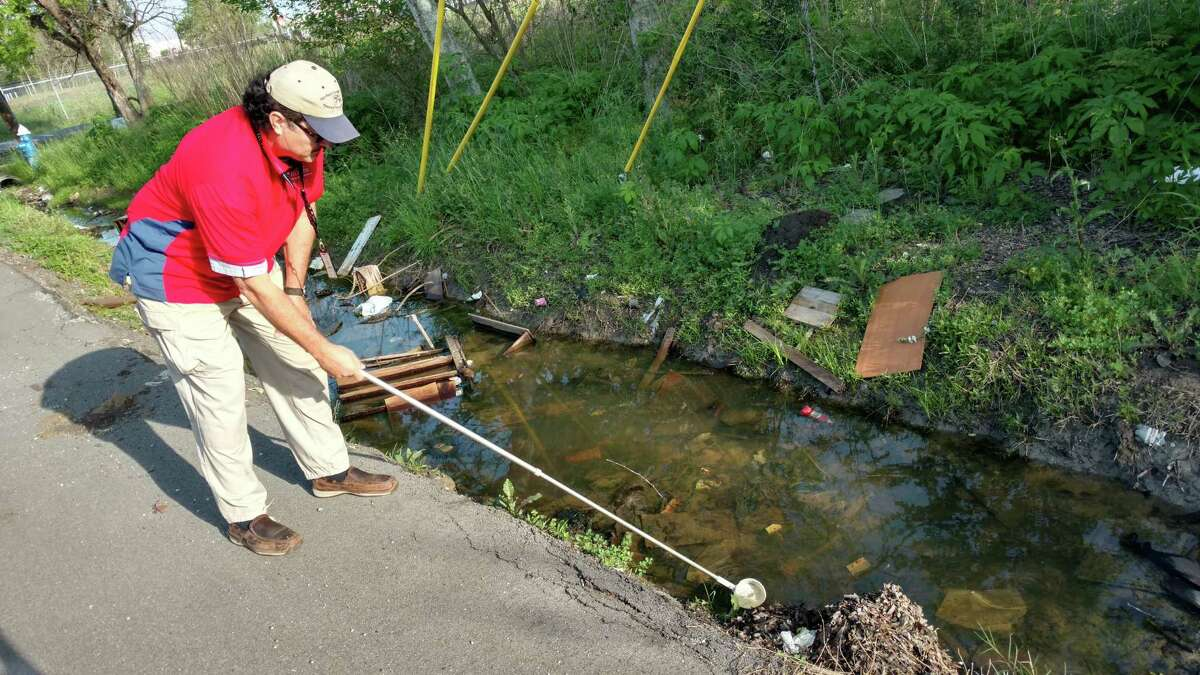 Salvador Rico, inspection supervisor with Harris County's Mosquito Control Division, examines standing water in a roadside ditch near SH-288 and Old Spanish Trail for larva, which can grow up to transmit disease.